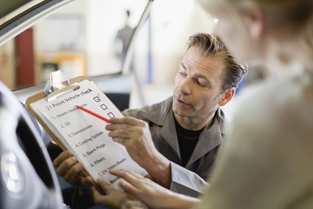 An inspector shows a list of vehicle check to a woman. Ask a professional pre-purchase car inspector in Melbourne to inspect your dream car. Contact German Precision now!