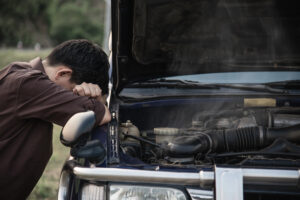 A stressed and sad man next to a broken car. Read this article to find out signs your car is a lemon. Never skip a pre-purchase car inspection in Melbourne. Call German Precision today!